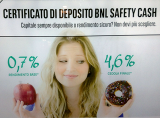 A woman holding an apple in one hand, donut in another, looking fondly at the donut