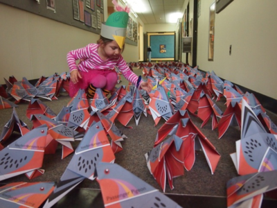 A young girl examines folded origami birds
