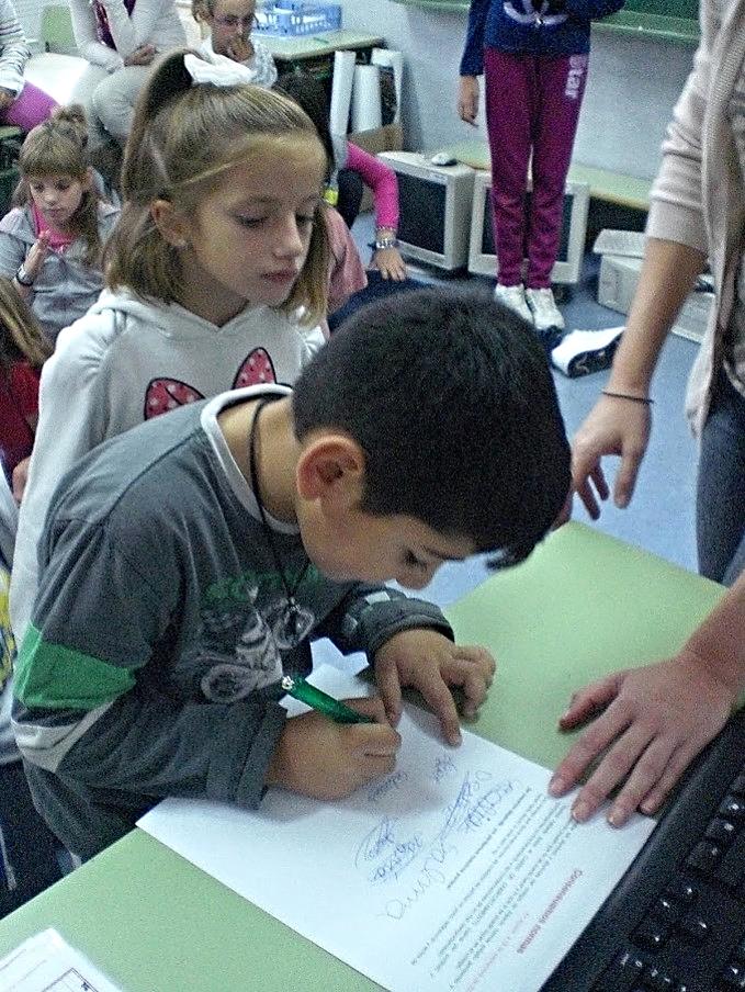 Alumno firmando el documento 'Consensuamos normas'. Colegio Público 'Ramón y Cajal' de Alpartir | Fondo documental del Colegio.