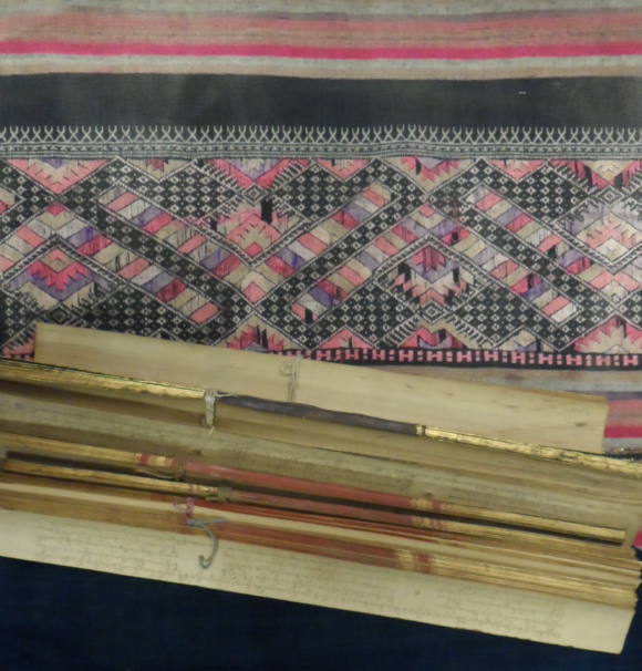 Bundles of palm leaves in Tham script with a hand-woven lady's skirt from northern Laos used as a manuscript wrapper, 19th or early 20th century. British Library, Or.16895.