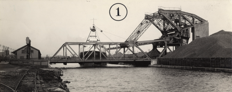 A black and white photo of a steel bridge over a ship channel with a ship in the background.