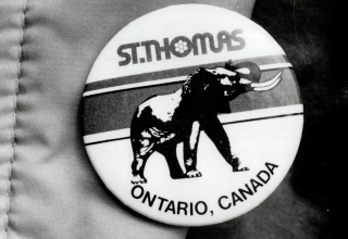 Black and white photo of a round pin with an image of an elephant on it and the words St. Thomas Ontario, Canada