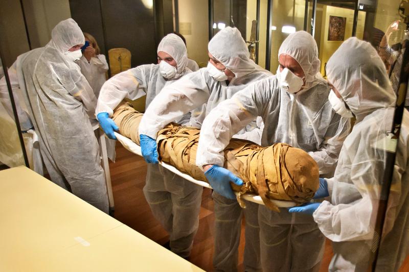 Los especialistas de la empresa TTI proceden a la extracción y traslado de una momia egipcia.