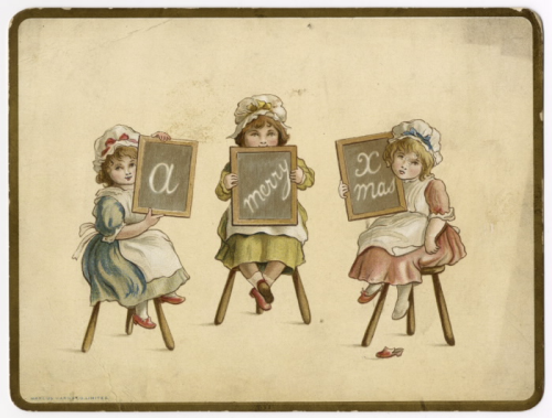 Three girls sitting on stools holding up chalk boards with a holiday message written on it