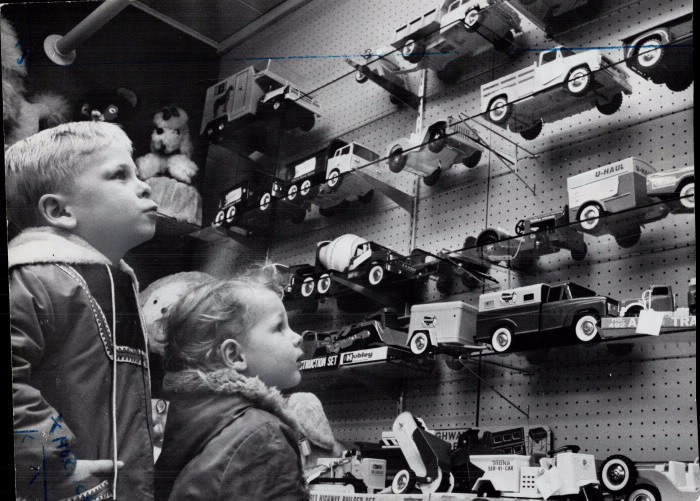 Boy and a girl stare longingly at toy trucks on the wall of a store
