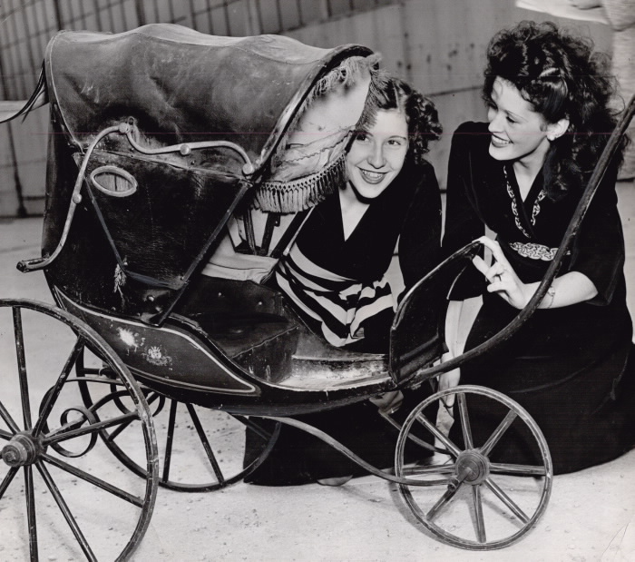 Two women look into an old fashioned stroller