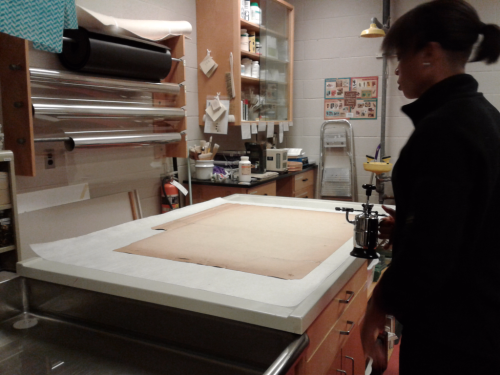 Large table in conservator lab with woman holding a tool with a nozzel