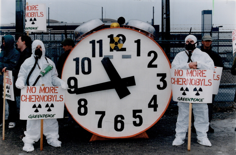 Greenpeace demonstrators donned in nuclear suits stand next to a nuclear doomsday clock